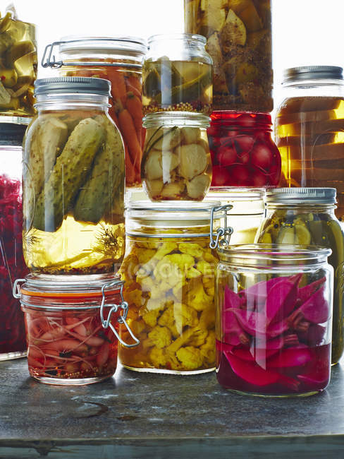 Various pickles in glass jars on table — Stock Photo