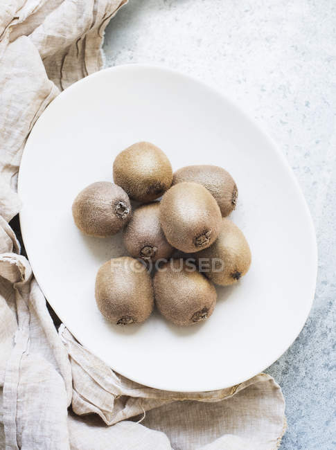 Plate of whole kiwi fruits — Stock Photo