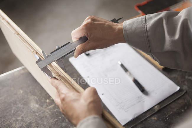 Carpenter measuring wood plank with vernier caliper in factory, Jiangsu, China — Stock Photo