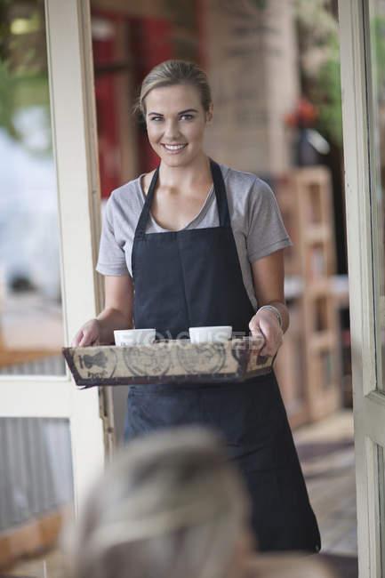 Молоді жінки офіціантка проведення лоток кавові чашки в кафе — стокове фото