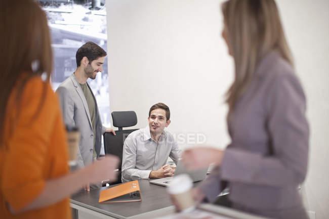 Colegas de negócios masculinos e femininos conversando no escritório — Fotografia de Stock