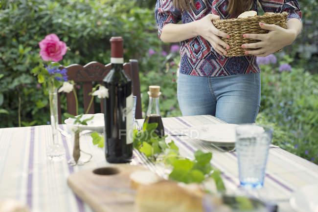 Обрезанное изображение женщины, Настройка таблицы в зеленом саду — стоковое фото