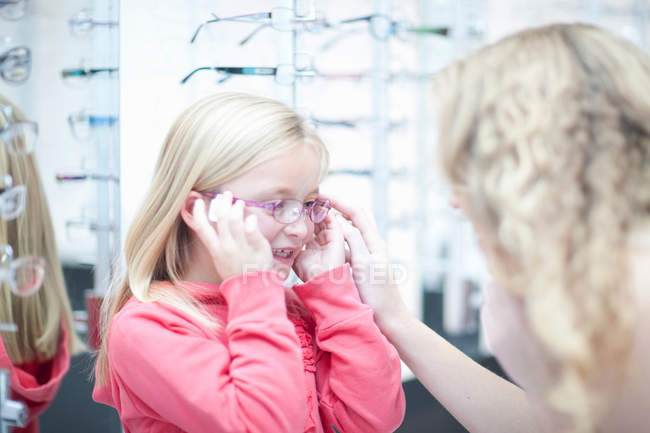 Young girl trying on eyeglasses — Stock Photo