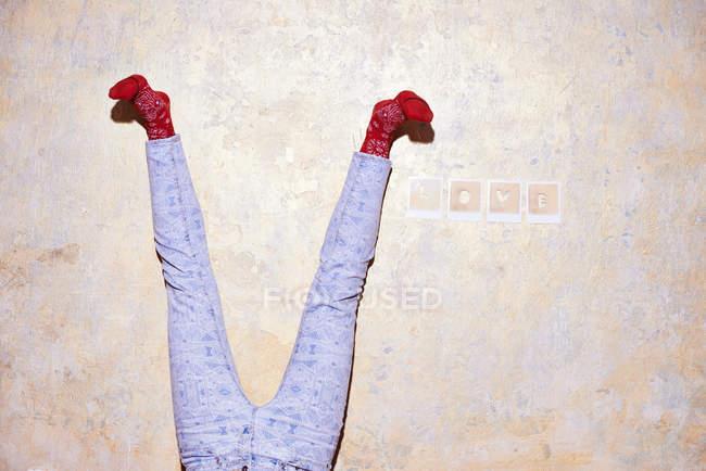 Студийный снимок молодых женщин ноги вверх ногами к стене — стоковое фото