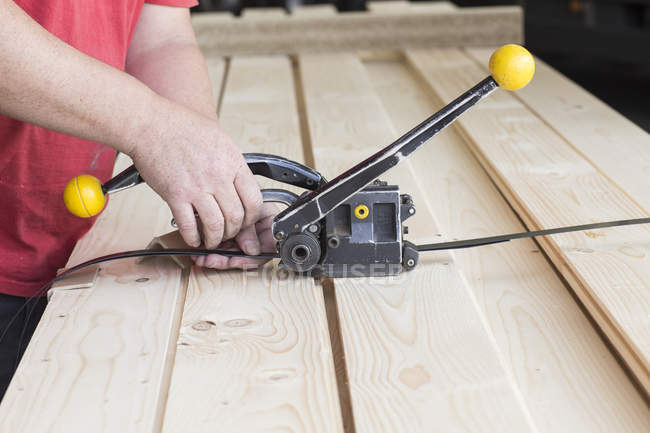 Close up of male warehouse worker fastening wooden planks in hardware store — Stock Photo