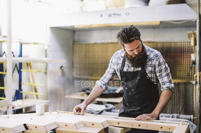 Cropped shot of mid adult craftsman measuring wood in organ workshop — Stock Photo