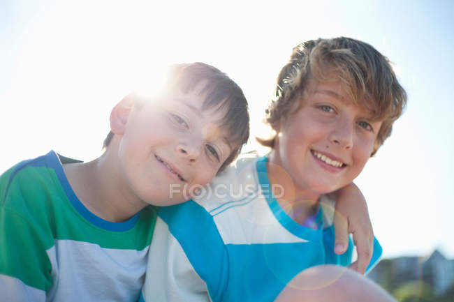 Smiling brothers hugging outdoors — Stock Photo