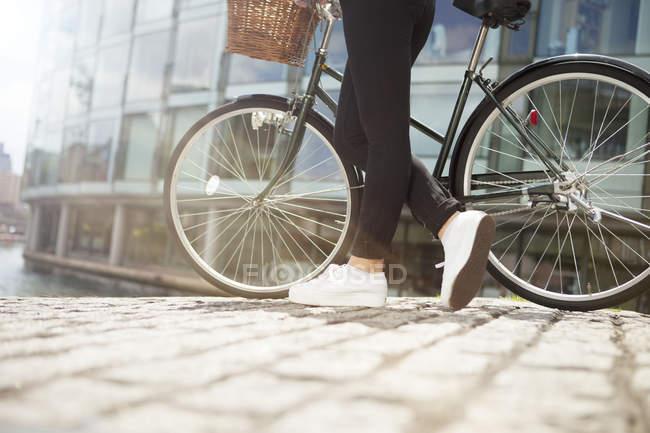 Жінка штовхає велосипеді уздовж каналу — стокове фото