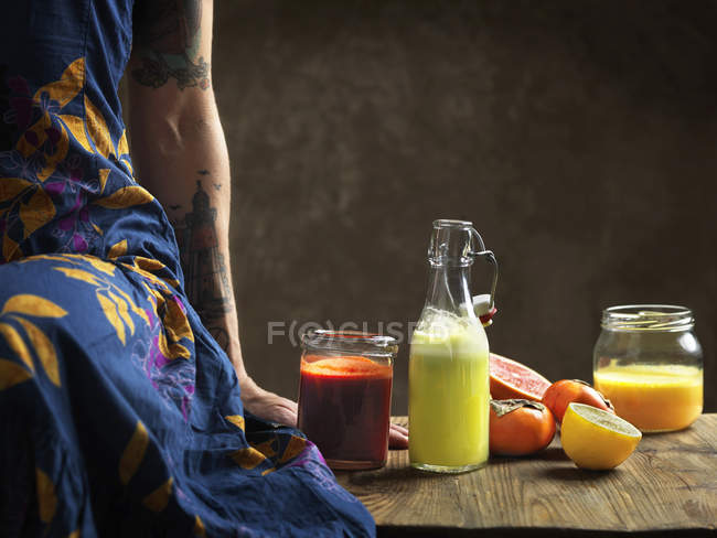 Vista cortada de mulher vestindo vestido sentado na mesa com sucos crus em garrafa de vidro e frascos — Fotografia de Stock