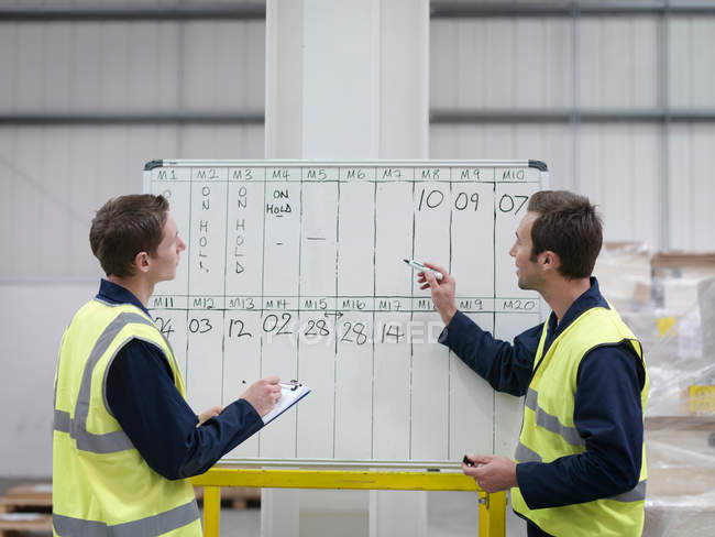 Workers With Whiteboard In Warehouse — Stockfoto