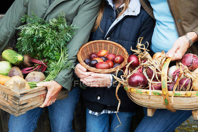 Cropped image of Family holding vegetables — Stock Photo