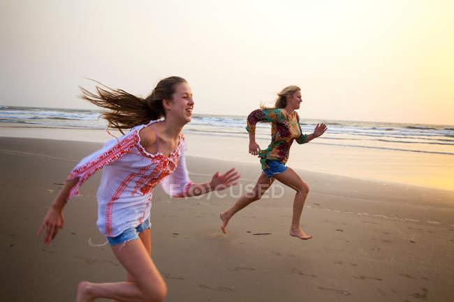 Мать и дочь бегут по пляжу на закате — стоковое фото