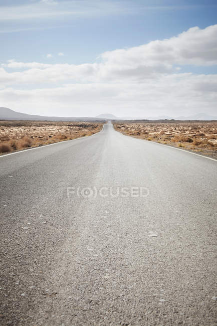 Paved road in rural landscape under cloudy sky — Stock Photo