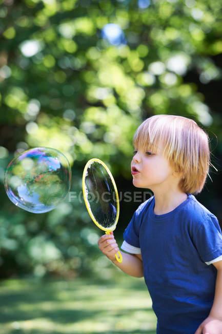 Junge übergroße Seifenblase im Hinterhof — Stockfoto
