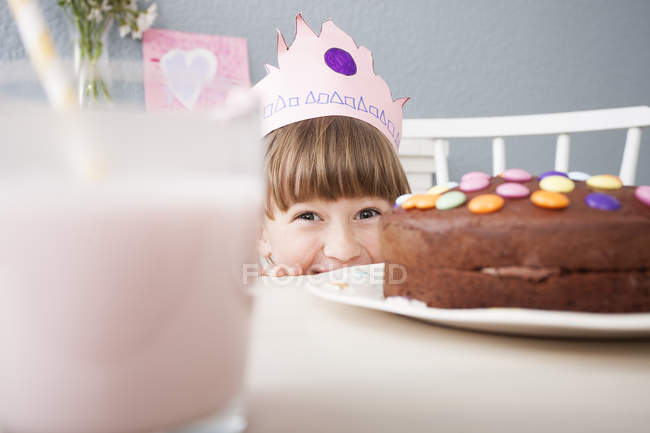 Girl in crown hiding behind birthday cake on table — Stock Photo