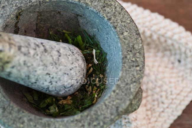 Ervas batendo em tigela de pedra, close-up tiro — Fotografia de Stock
