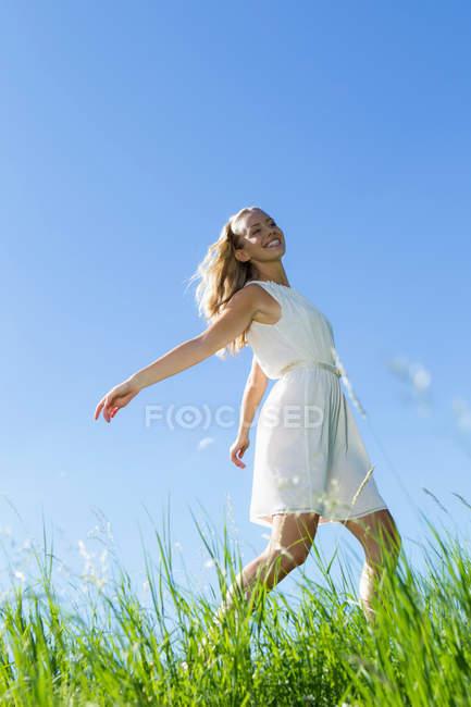Улыбающаяся женщина ходит в высокой траве — стоковое фото