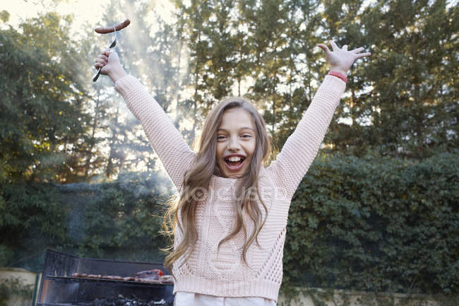 Girl arms raised holding sausage on fork looking at camera smiling — Stock Photo