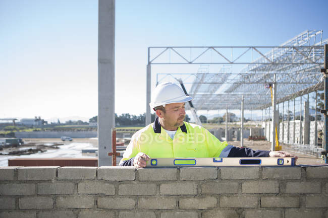 Builder using spirit level on construction site wall — Stock Photo