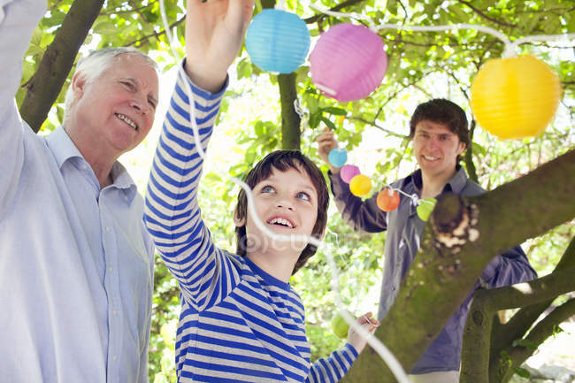 Three generation family putting fairy lights in tree — Stock Photo