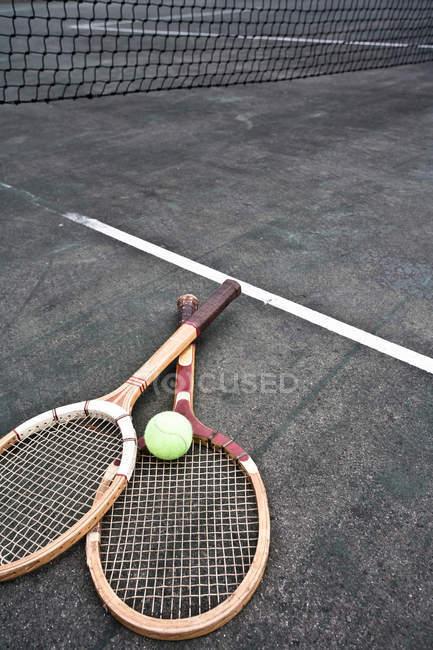 Raquetas de tenis y pelota en cancha bajo red - foto de stock