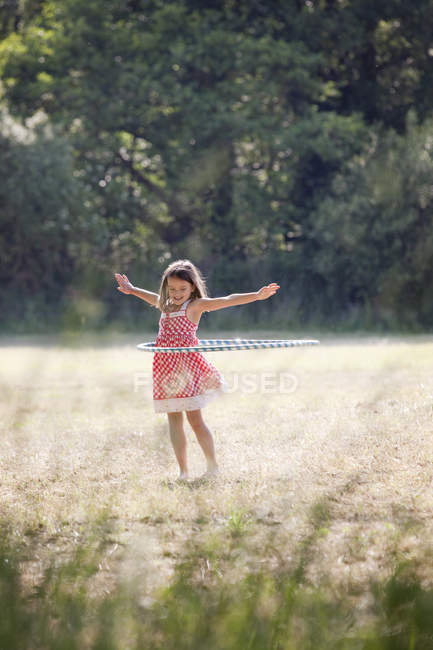 Girl with hula hoop in country field — Stock Photo