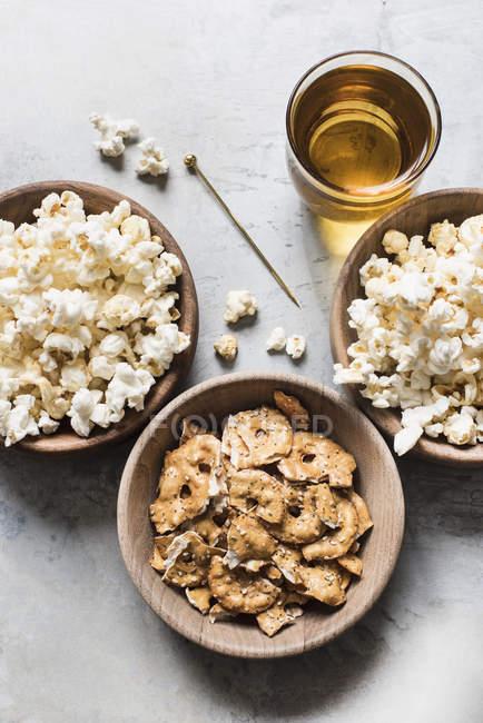 Миски попкорн і кренделі крекери — стокове фото