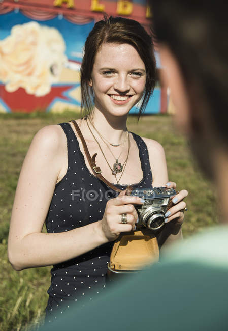 Young couple taking photographs on SLR camera at funfair — Stock Photo