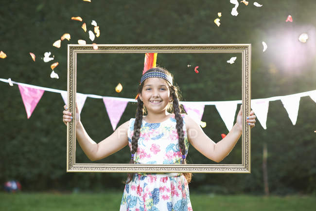 Portrait of girl looking through picture frame, smiling at camera — Stock Photo