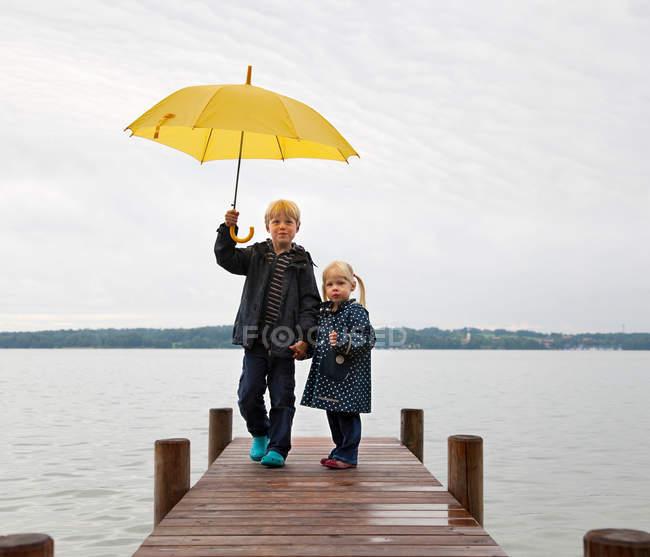 Enfants avec parapluie jaune sur quai — Photo de stock