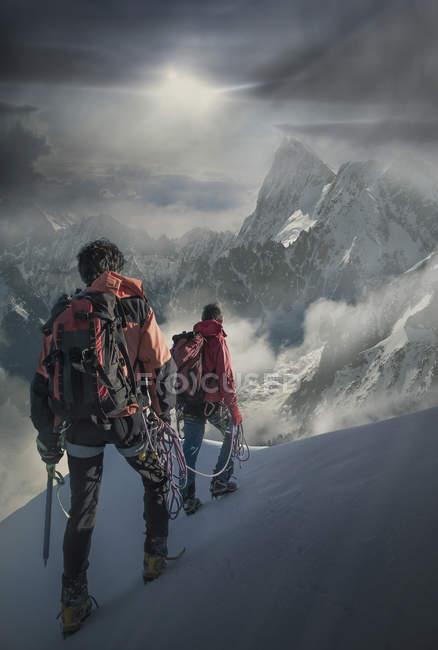 Due scalatori su un pendio innevato che osservano i Grand Jorasses, nel massiccio del Monte Bianco, Chamonix, Francia — Foto stock