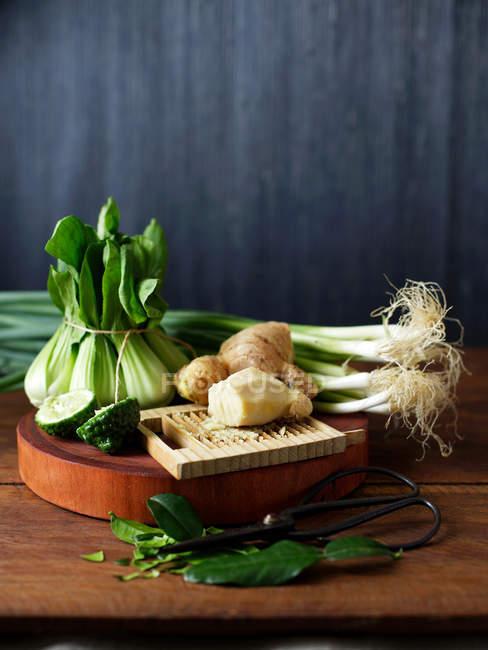 Бок-чой, каффир лайм, имбирь, лук шалот и весенний лук на столе — стоковое фото