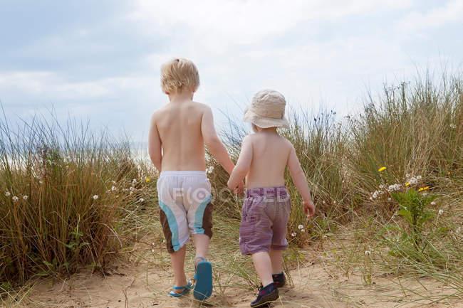 Хлопчики тримає руки в трав'янистих піску — стокове фото