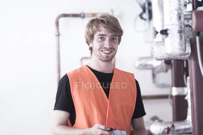 Молодой человек в котельной в бронежилете с высокой видимостью смотрит в камеру улыбаясь — стоковое фото