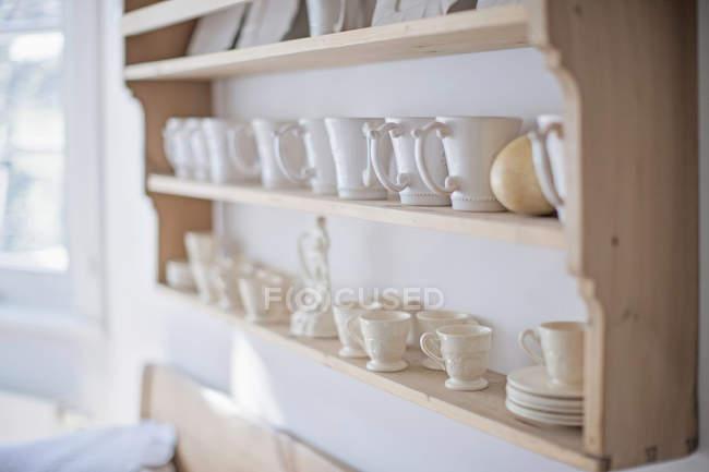 Milchkaffee Tassen auf hölzernen Küchenregal — Stockfoto