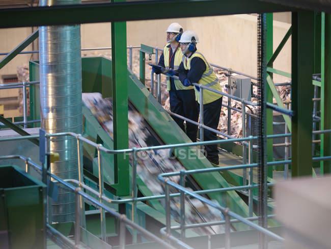 Робітники з видом на завод утилізувати — стокове фото