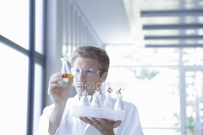Male scientist analyzing erlenmeyer flask in lab — Stock Photo
