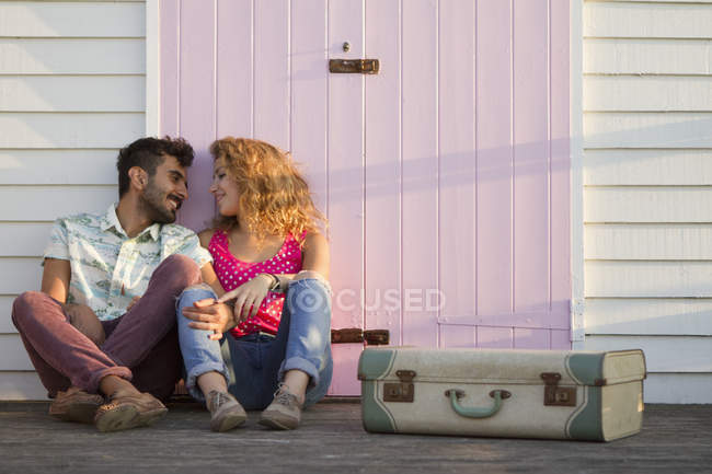 Young couple sitting by beach hut with suitcase — Stock Photo