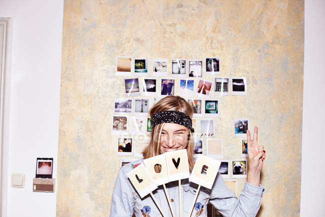 Young woman in front of photo wall holding up love and peace signs — Stock Photo