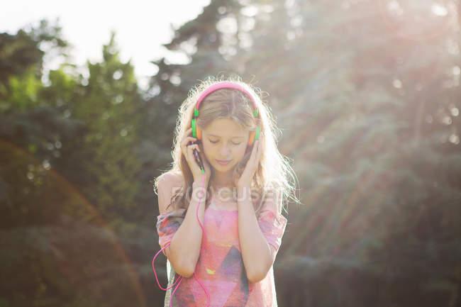 Teenage girl wearing headphones in sunlight — Stock Photo