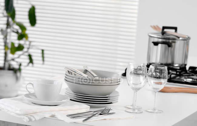 Empilhados de pratos e talheres na mesa — Fotografia de Stock