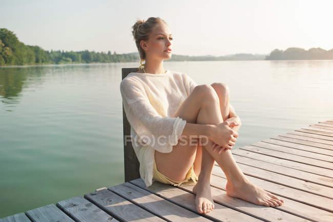 Mujer joven sentada en el muelle del lago - foto de stock