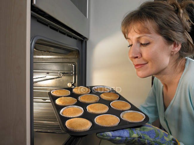 Woman baking cupcakes in kitchen — Stock Photo