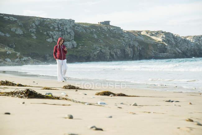 Зрелая женщина пишет смс на смартфоне во время прогулки по пляжу, Камаре-сюр-мер, Бриттани, Франция — стоковое фото