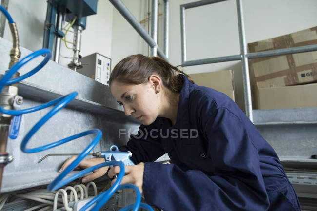 Female engineer leaning forward to inspect cables in factory — Stock Photo