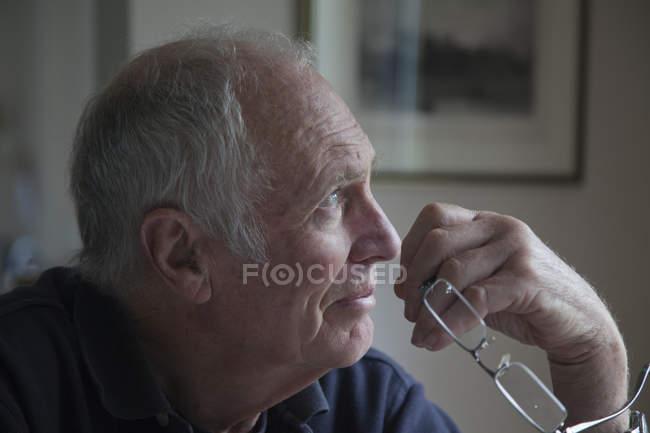Uomo senior, che tiene gli occhiali, che osserva dalla finestra — Foto stock