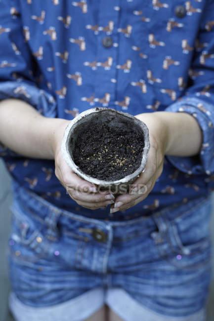 Close up de menina segurando vaso de flores com sementes, tiro cortado — Fotografia de Stock