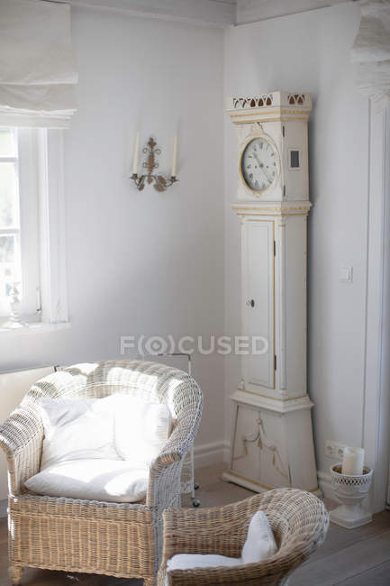 Wicker chairs and clock in living room — Stock Photo
