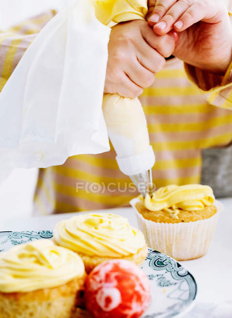 Hands icing cupcake on table, cropped shot — Stock Photo