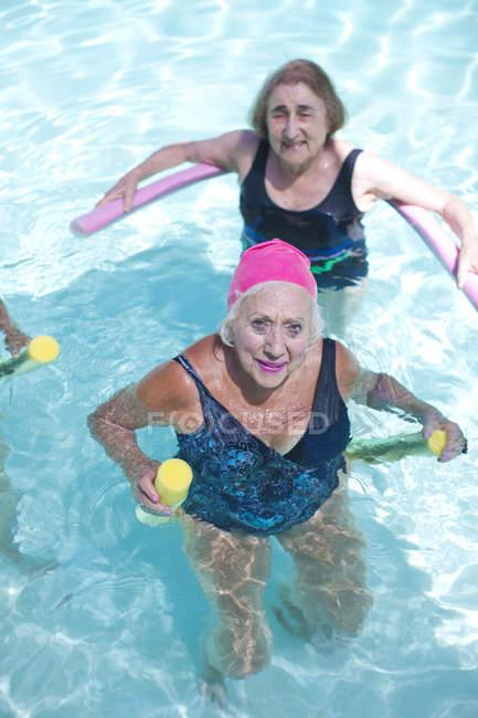 Portrait of senior women doing exercise in swimming pool — Stock Photo